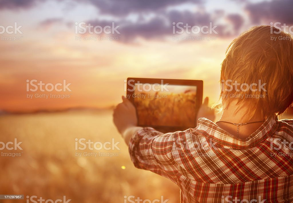 Young girl take a photo at digital tablet outdoors royalty-free stock photo