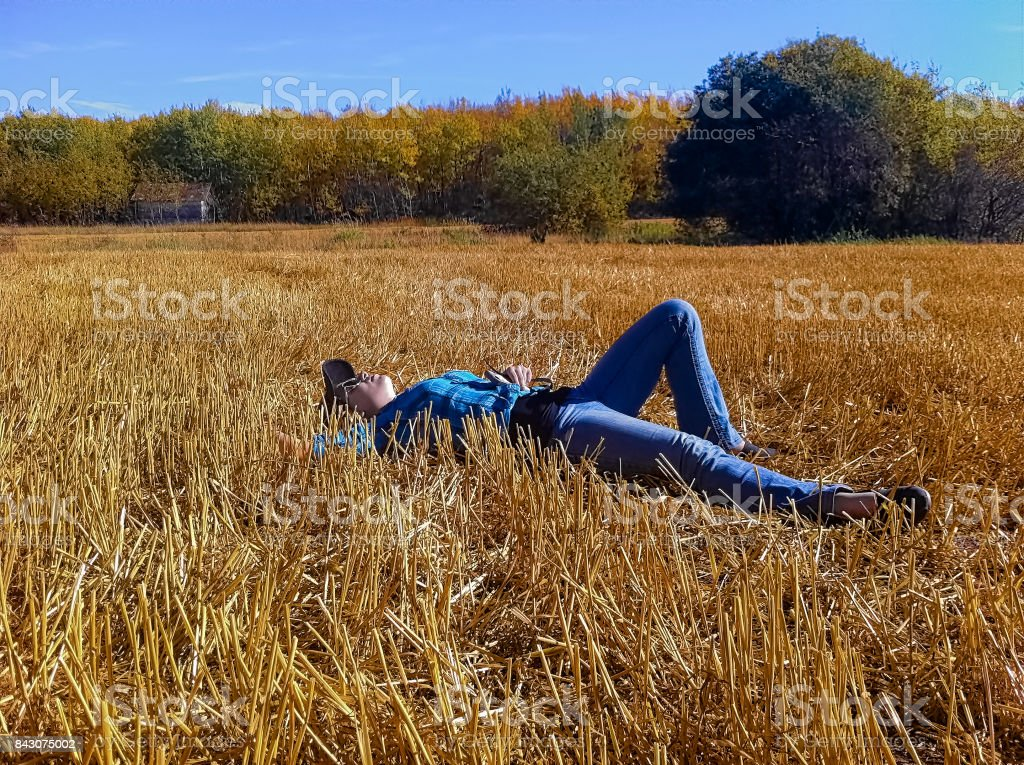 A young girl taking a break while working on a farm, laying down in a straw field looking up at the sky stock photo
