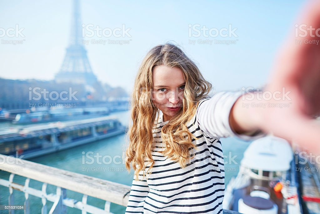 Young girl taking selfie near the Eiffel tower stock photo