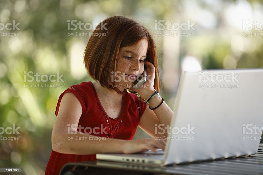 Young girl talking on cell phone while using laptop computer royalty-free stock photo