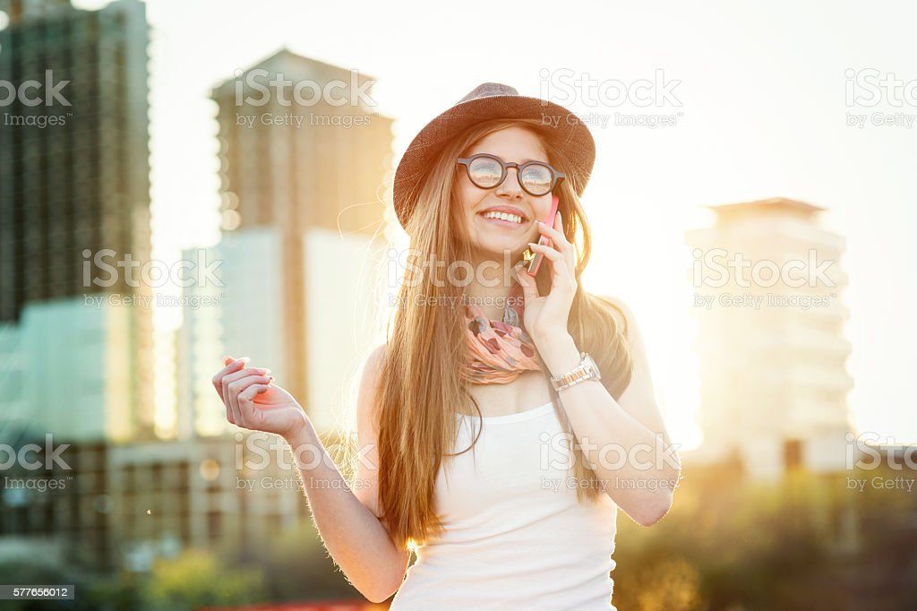 Young girl talking on the cell phone in the city stock photo