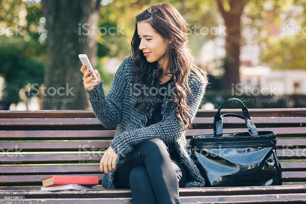 Young girl texting on a smart phone stock photo