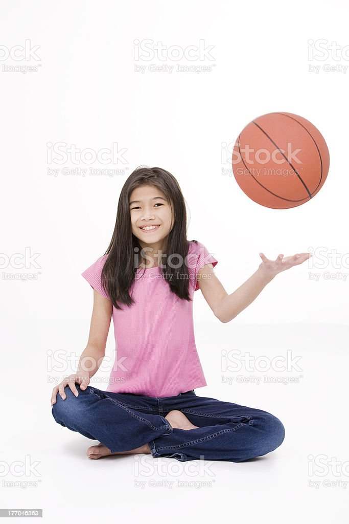 Young girl throwing basketball, isolated on white stock photo