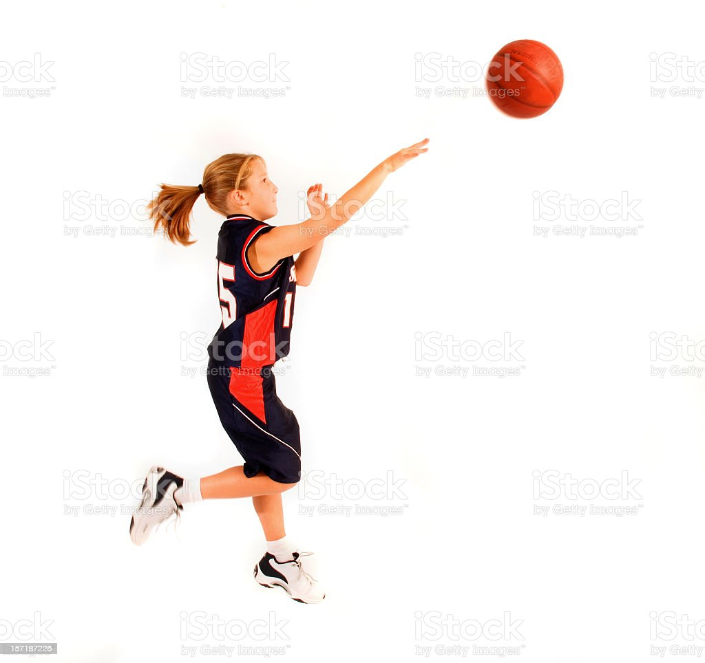 Young girl throwing basketball stock photo