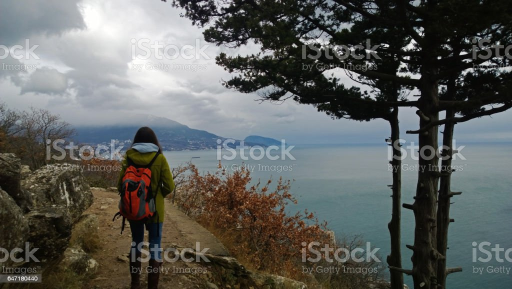 Young girl traveler with backpack standing looking into the distance at the beautiful view of the sea and cliffs. stock photo