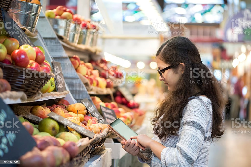 Young Girl Using Computer Tablet to Shop at Produce Market stock photo