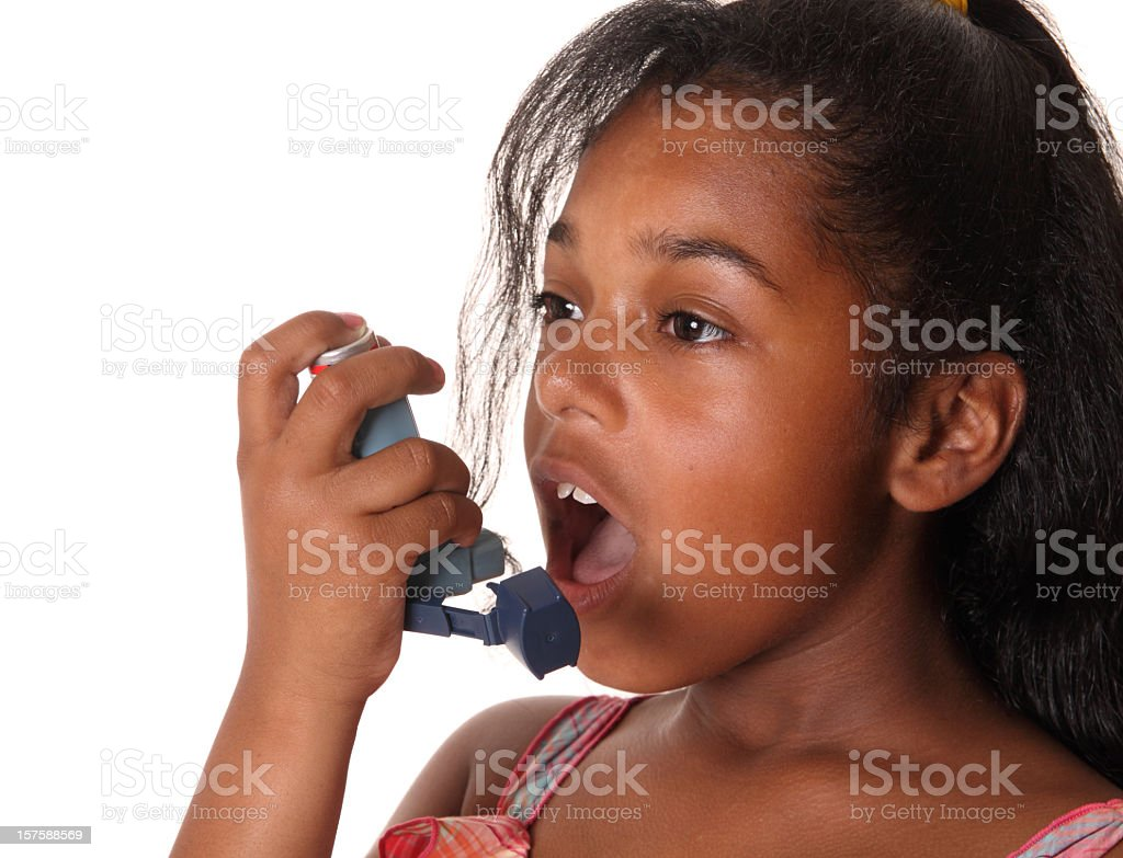 Young girl using her blue inhaler stock photo