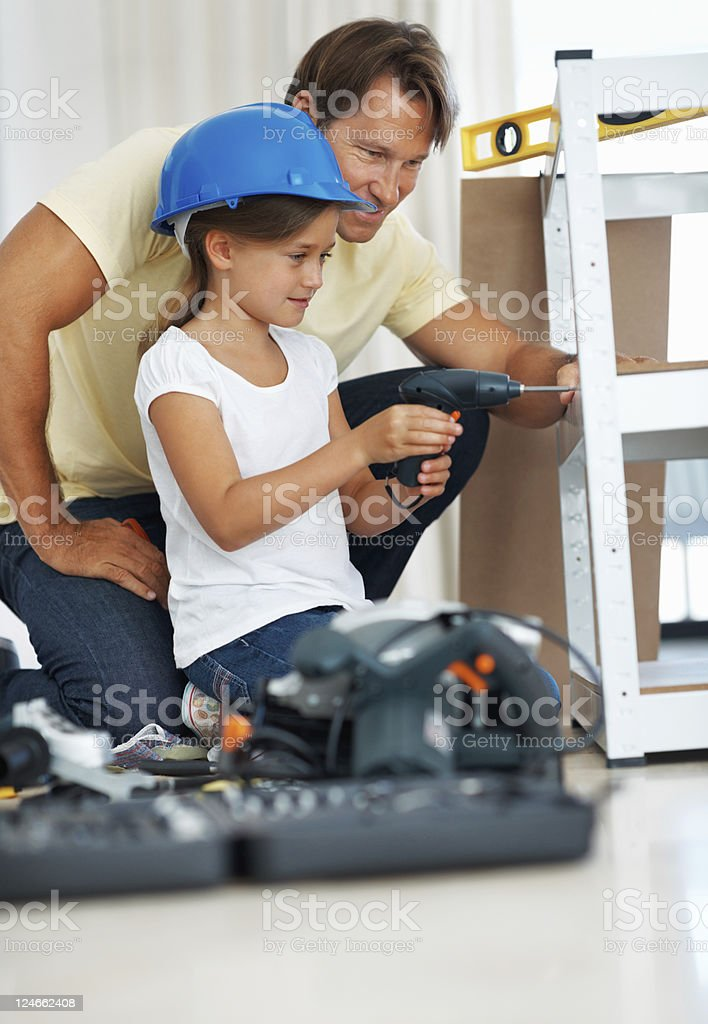 Young girl using power drill with father assisting her royalty-free stock photo