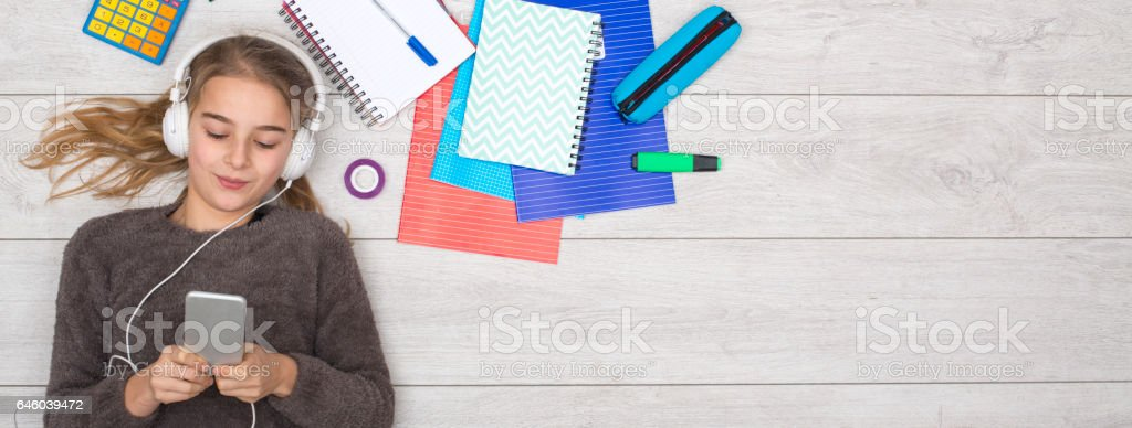 young girl using smart phone with homework stock photo
