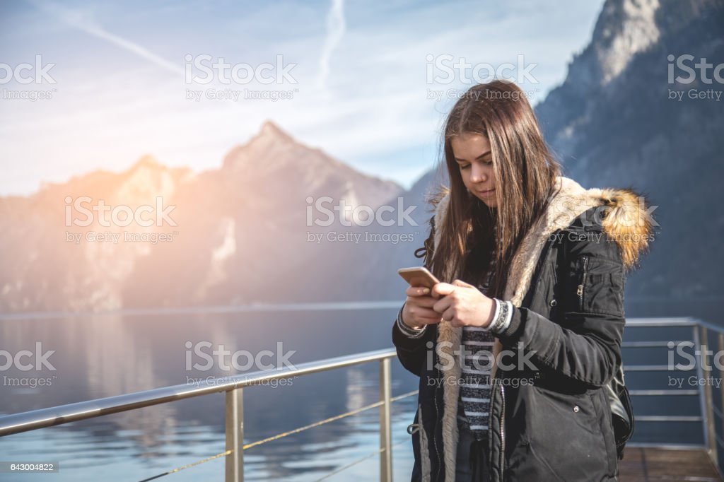 Young girl using smartphone in nature near lake stock photo