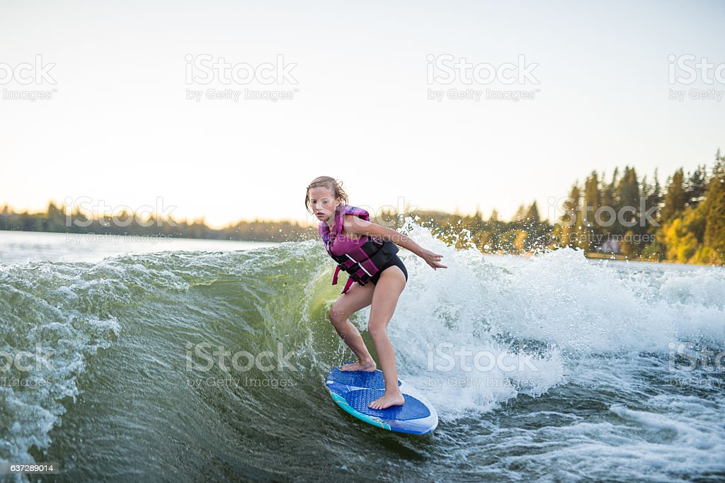 Young girl wakesurfing at sunset on giant wake stock photo