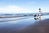 young girl walk with siberian at the beach