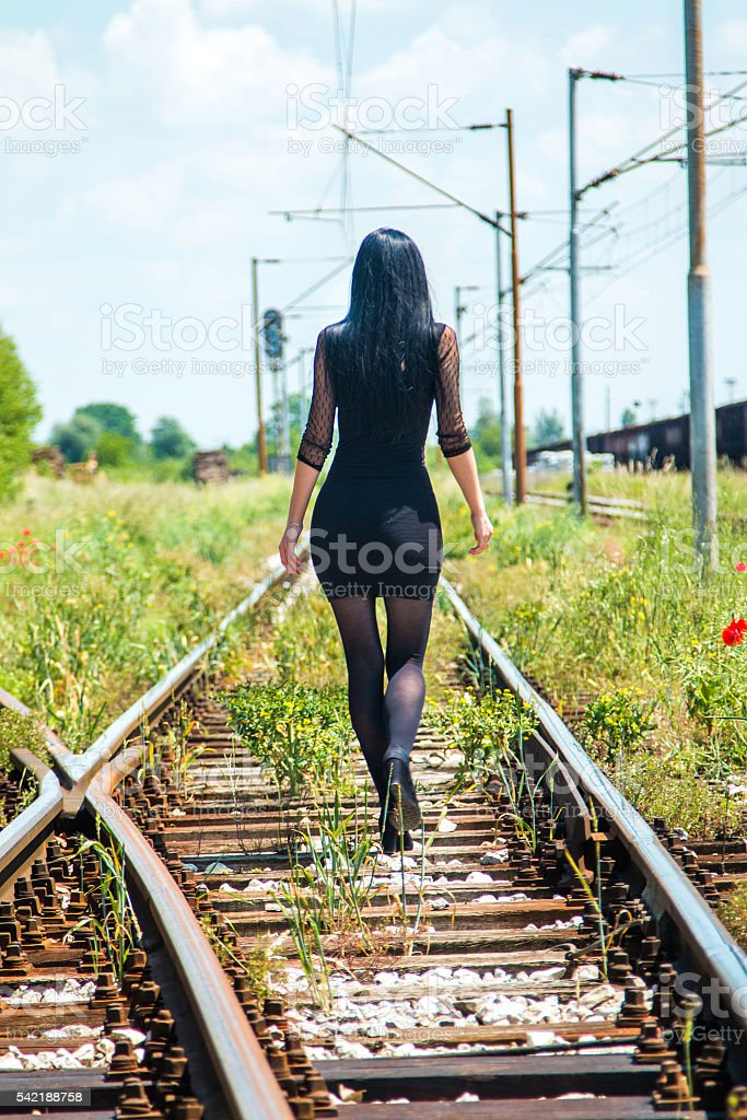 Young girl walking down rail tracks stock photo