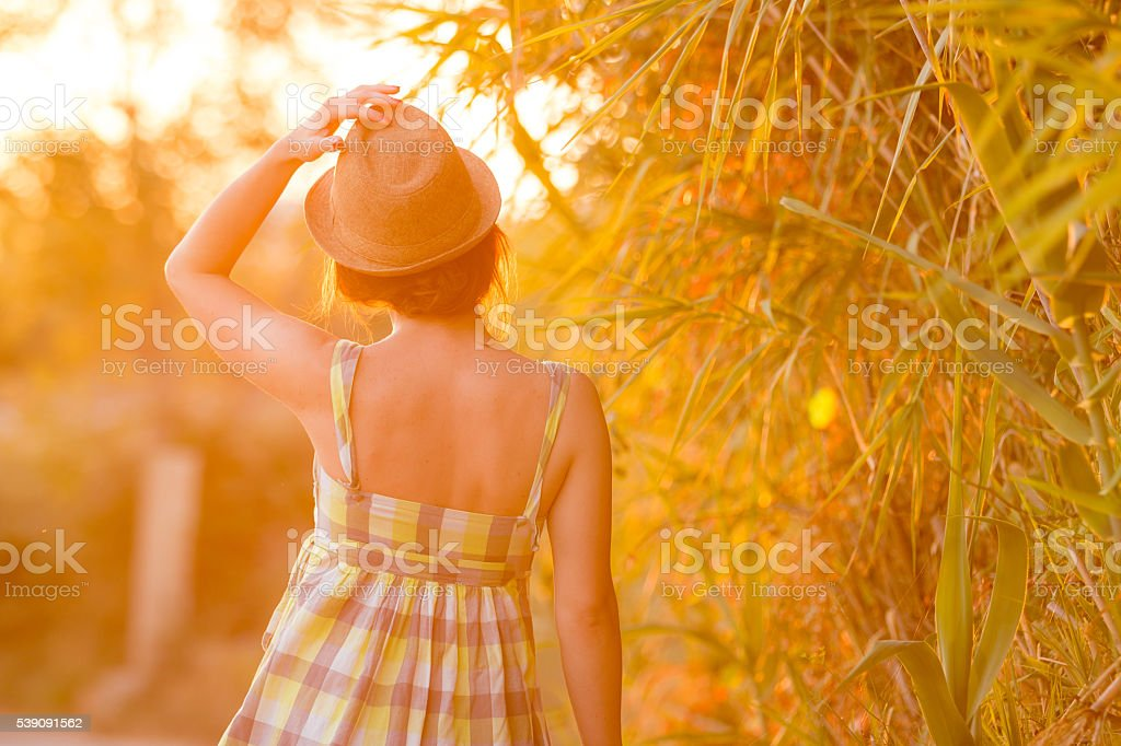 Young girl walking in sunset. stock photo