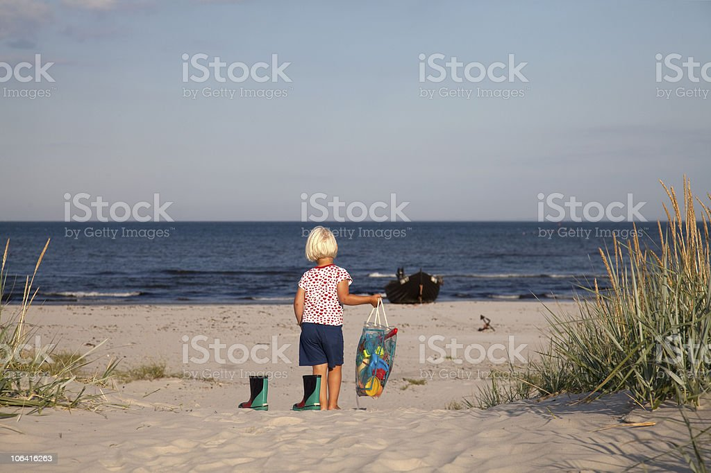 young girl walking to the beach stock photo