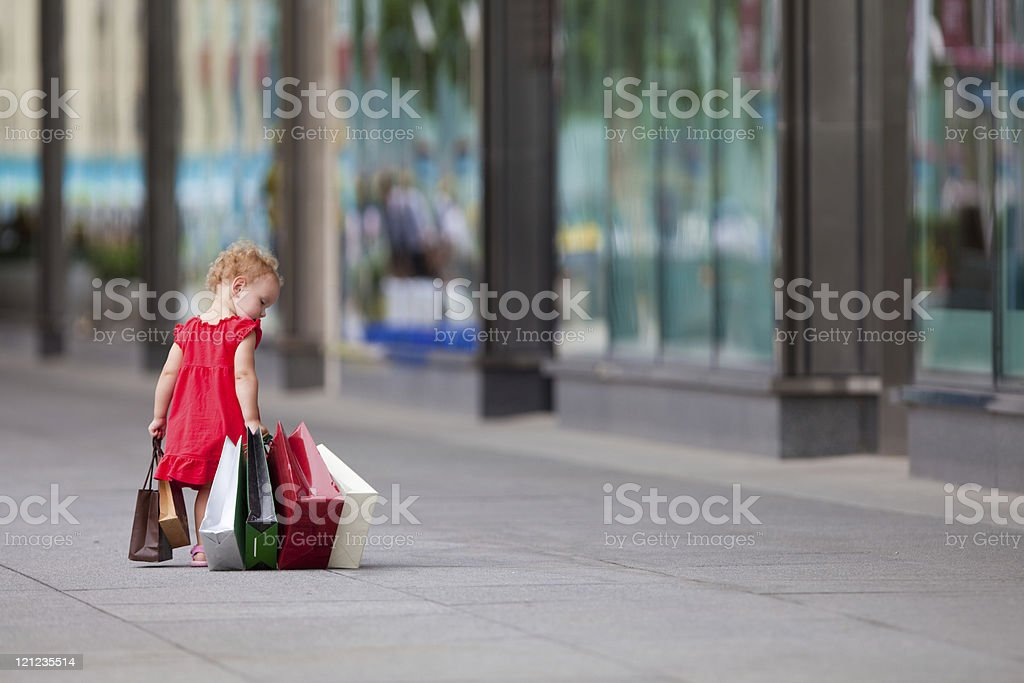 Young girl walking with a bunch of bags stock photo