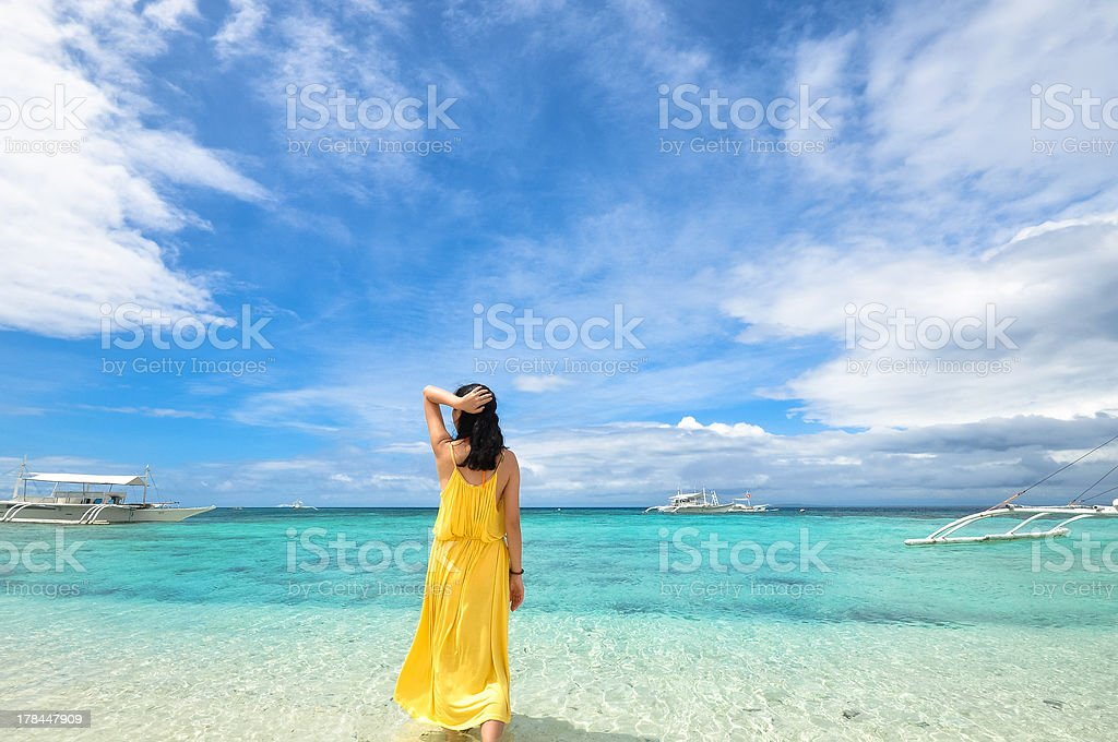 young girl walks in shallow water on tropical beach royalty-free stock photo