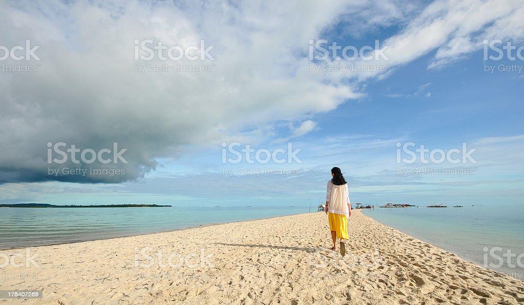 young girl walks on long narrow beach royalty-free stock photo