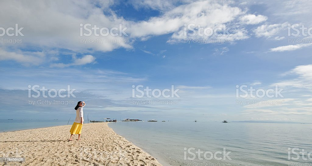 young girl walks on long narrow beach royalty-free stock photo