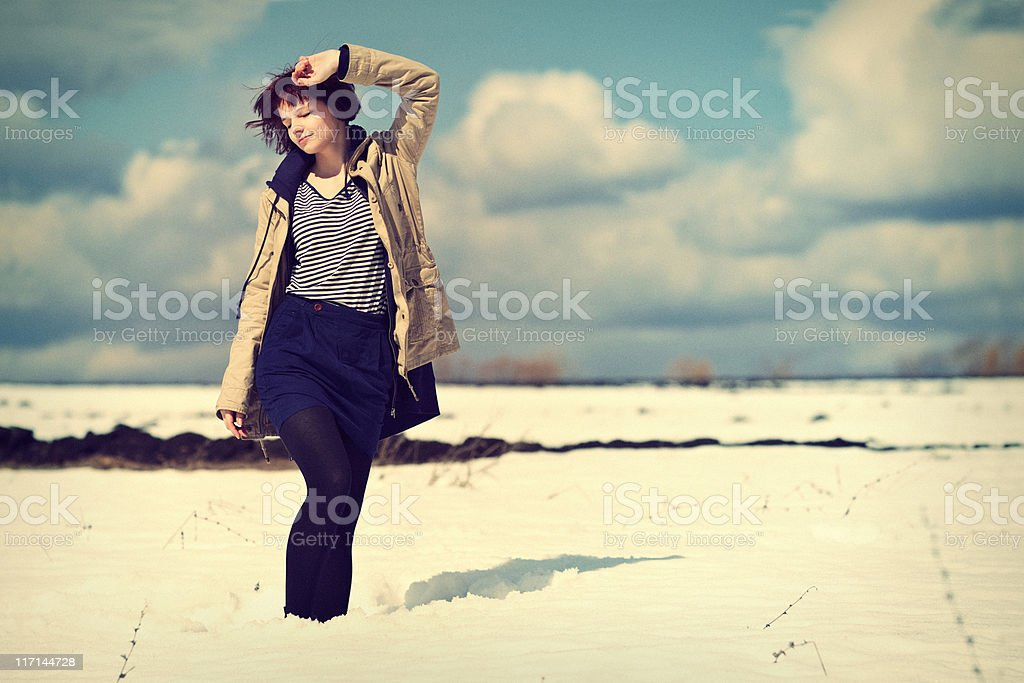 Young girl walks through the snow in spring royalty-free stock photo
