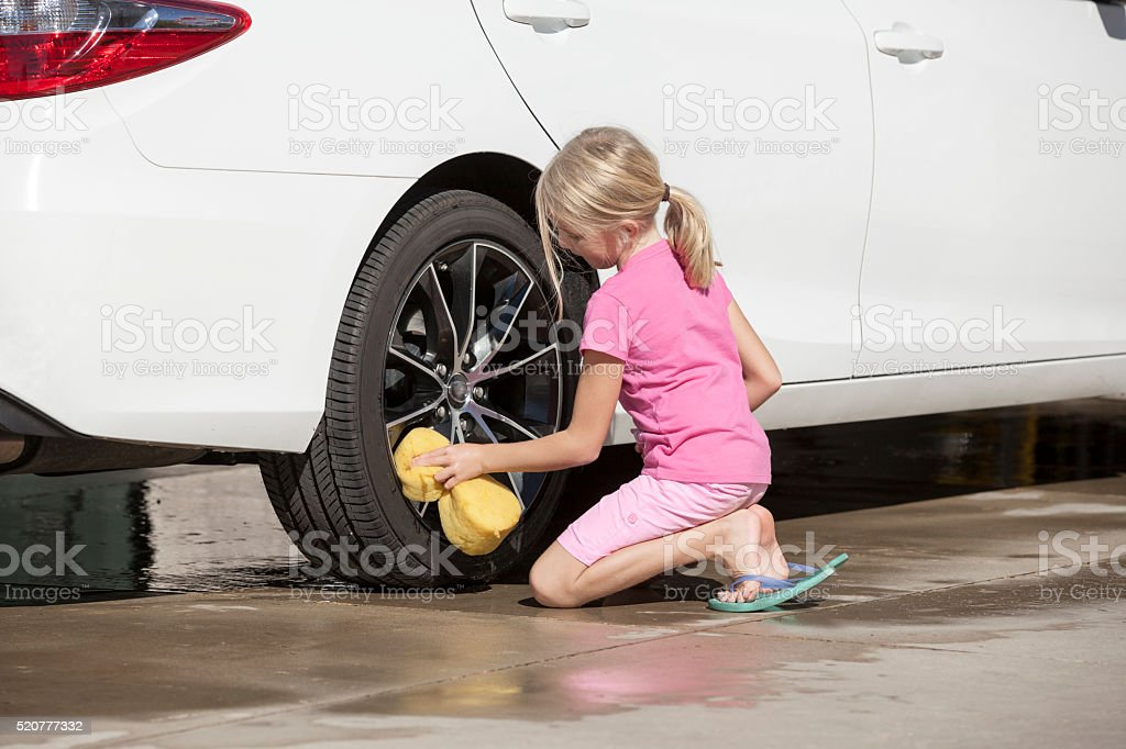 Young Girl Washing a Car Wheel in the Driveway stock photo