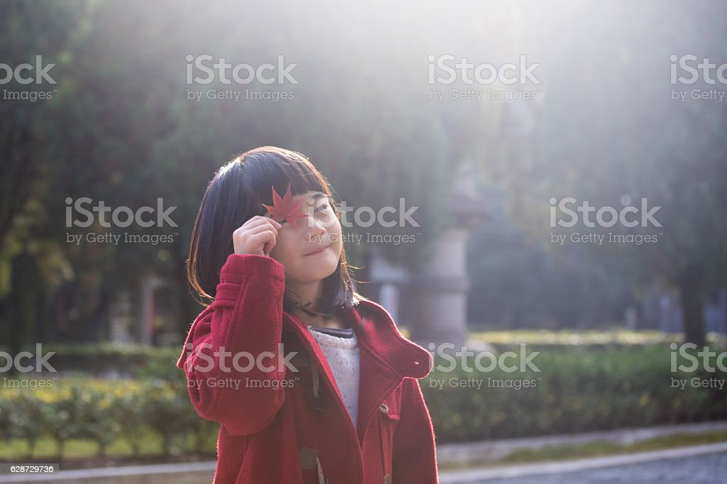 Young girl watching through maple leaf stock photo