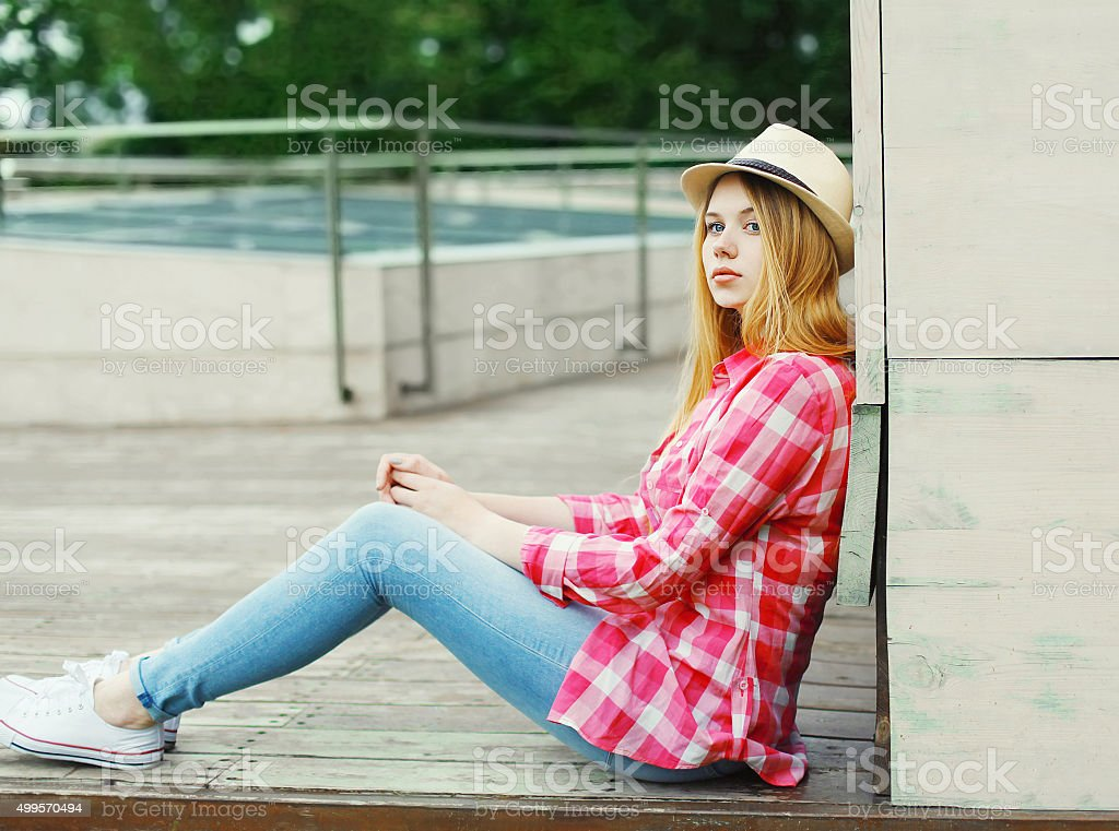 young girl wearing a pink shirt and summer hat sitting stock photo