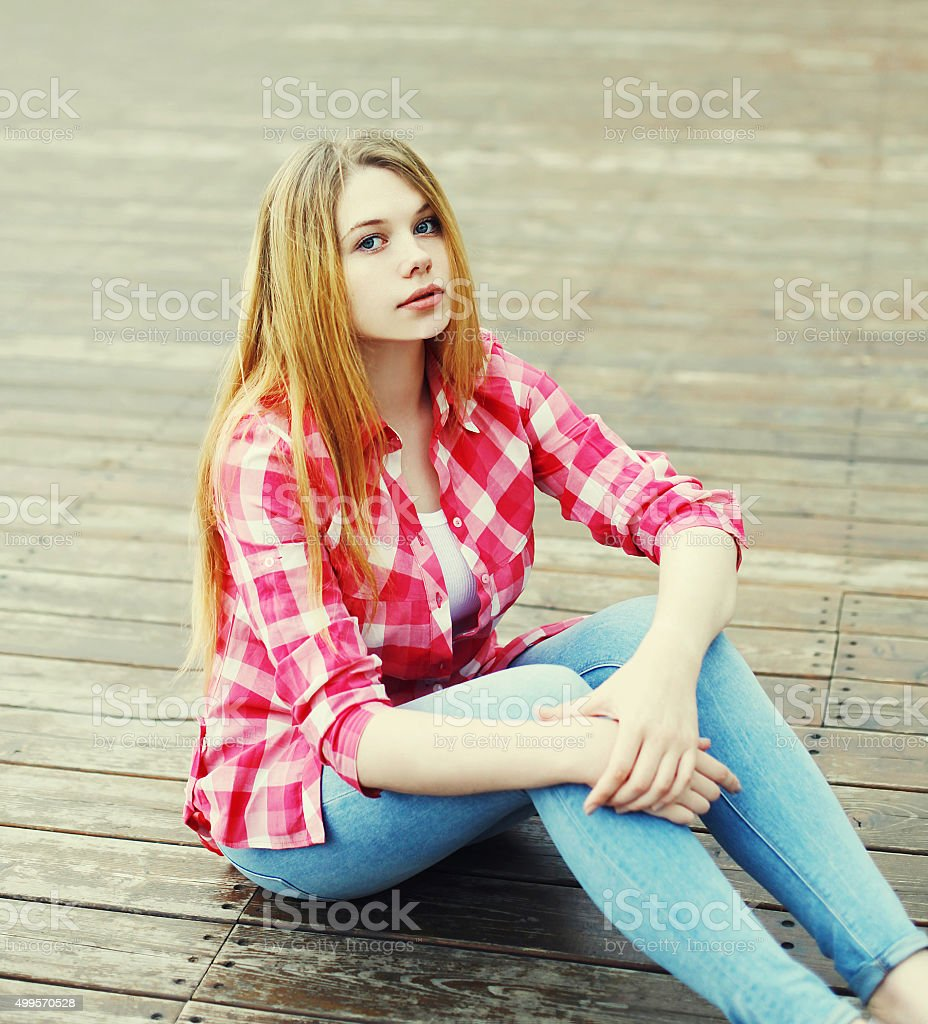 young girl wearing a pink shirt sitting resting in city stock photo