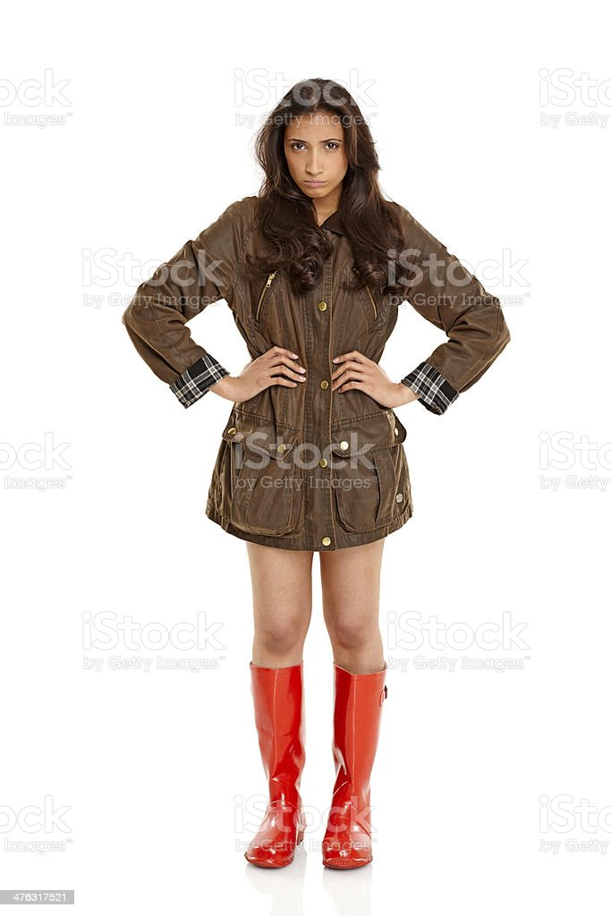 Young girl wearing coat and gumboots looking upset royalty-free stock photo