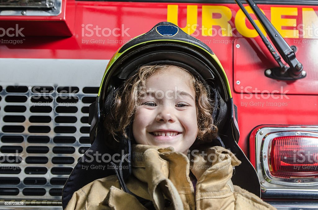 Young girl wearing fireman coat and helmet stock photo