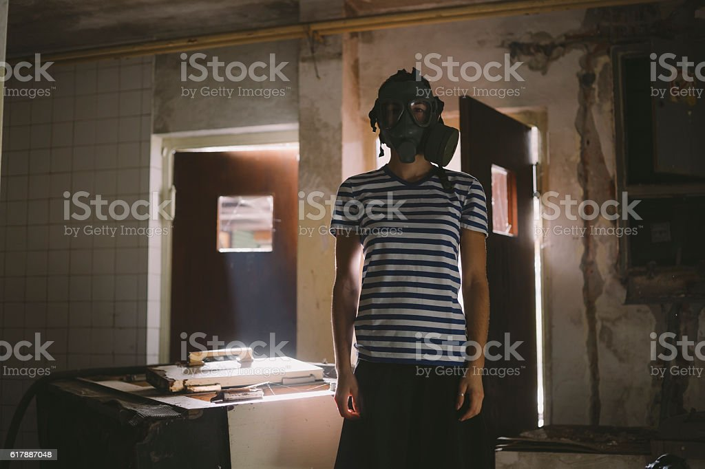 Young girl wearing gas mask inside of abandoned ruined building stock photo