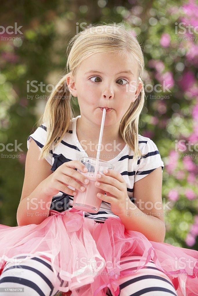Young Girl Wearing Pink Wellington Boots Drinking Milkshake stock photo