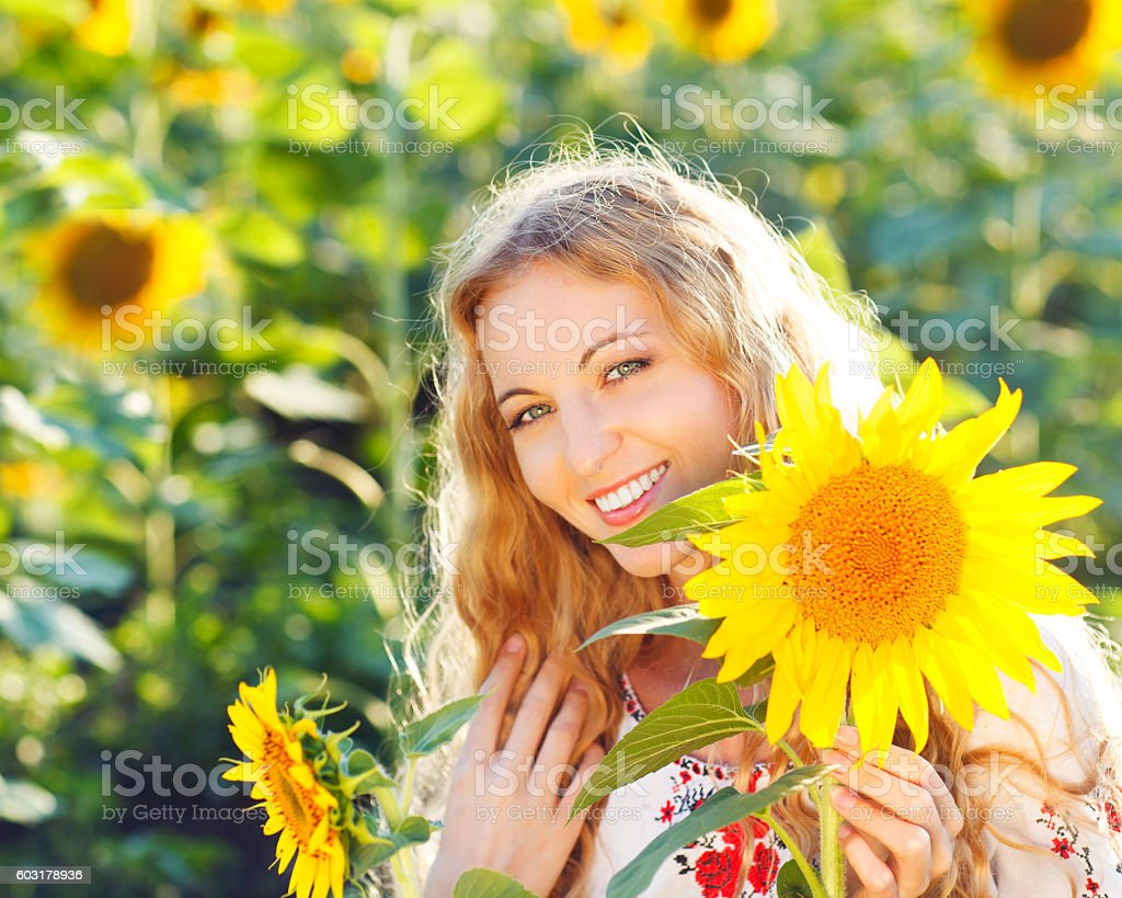 Young girl wearing traditional blouse holding sunflower stock photo