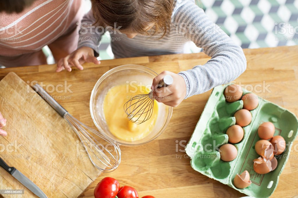 Young girl whipping eggs in a bow stock photo