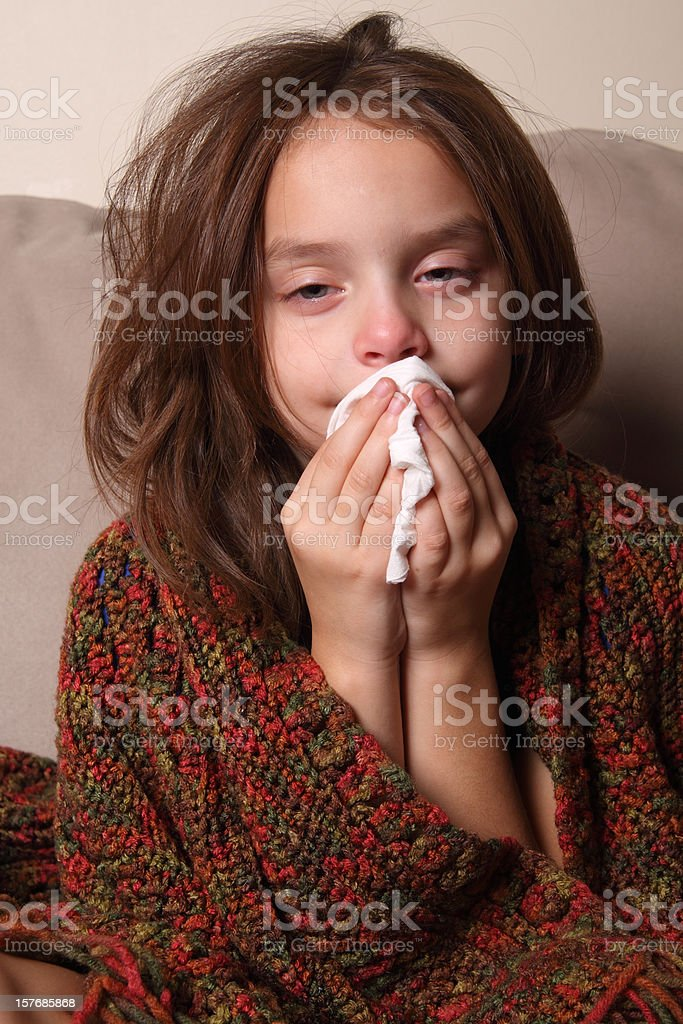Young girl with a cold blowing her nose  stock photo