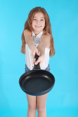 Young girl with a frying pan