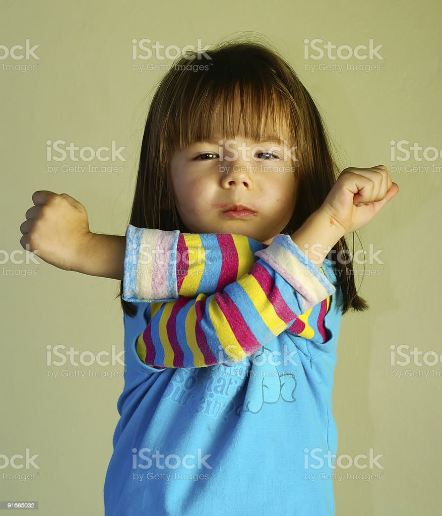 Young girl with a grumpy face crossing her arms stock photo