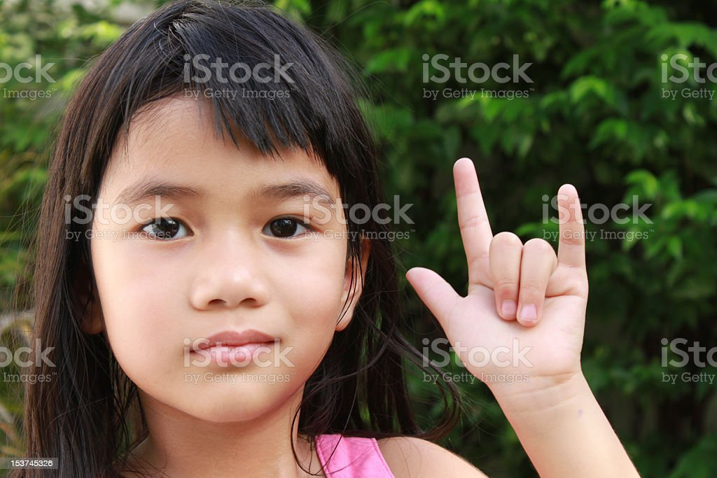 A young girl with a hand sign saying I love you stock photo