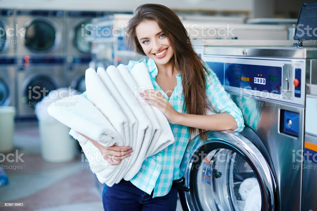 Young girl with a heap of fresh linen stock photo