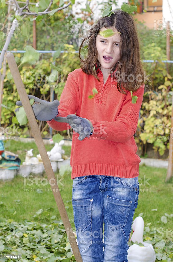 Young girl with a rake tool cleaning garden green leafs royalty-free stock photo