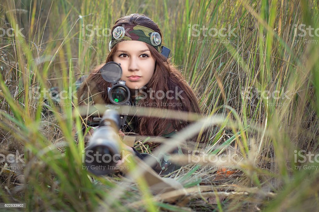 Young girl with a rifle peeking out of the grass stock photo
