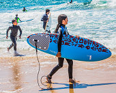 Young girl with a surfboard at the beach