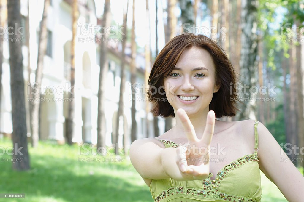 Young girl with a victory sign at the park royalty-free stock photo