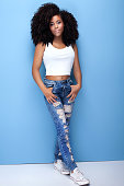 Young girl with afro posing on blue background.