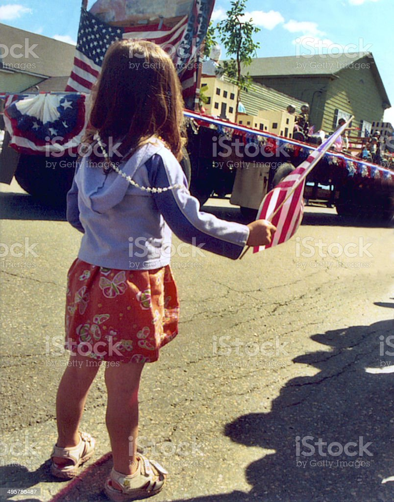 Young girl with American flag at parade stock photo