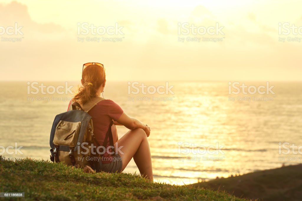 Young girl with backpack enjoying sunset listening to music on peak of mountain. stock photo