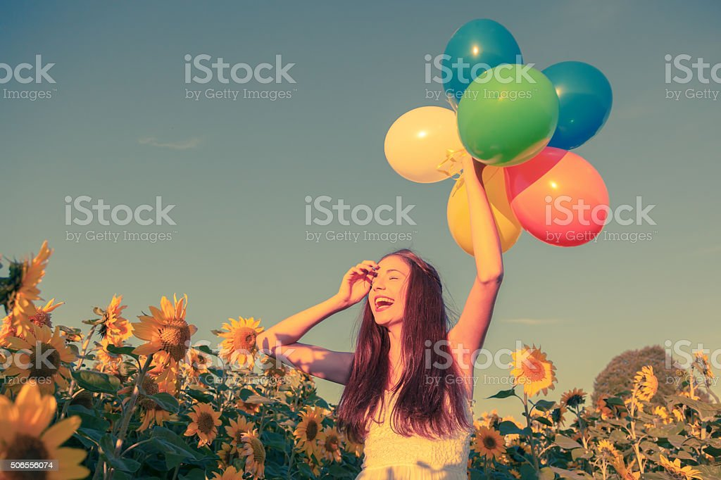 young girl with balloons in a sunflower field stock photo