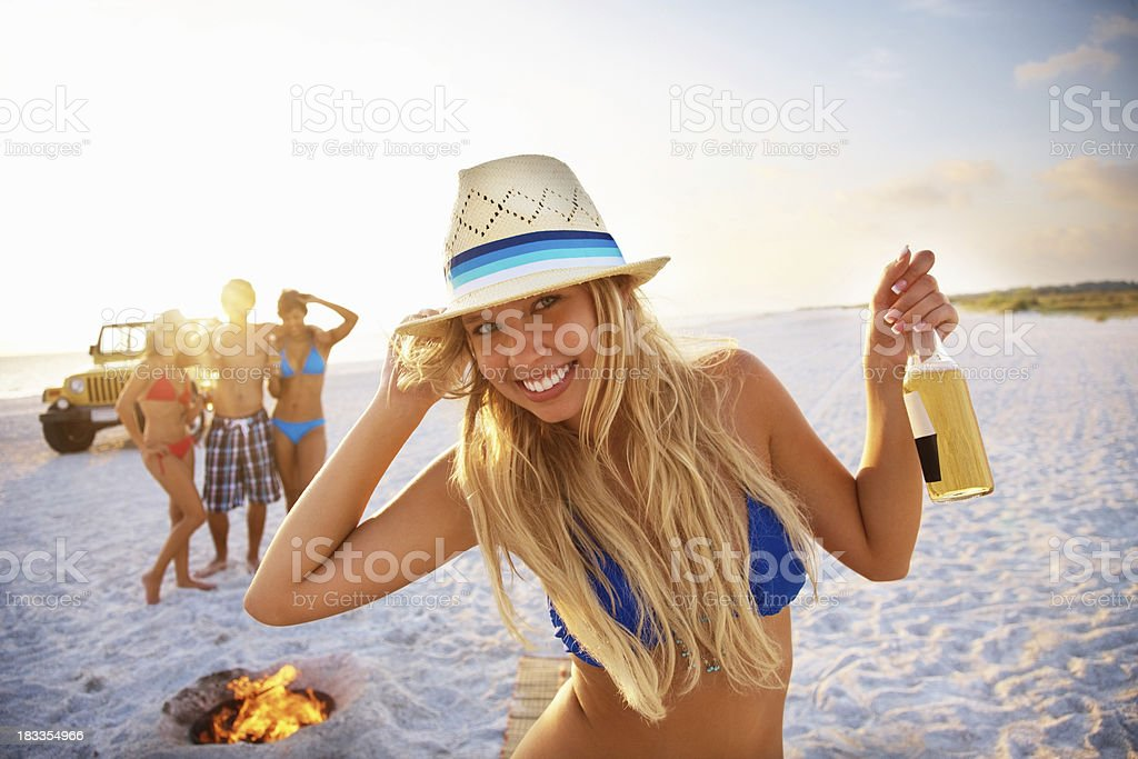 Young girl with beer dancing and her friends in background royalty-free stock photo