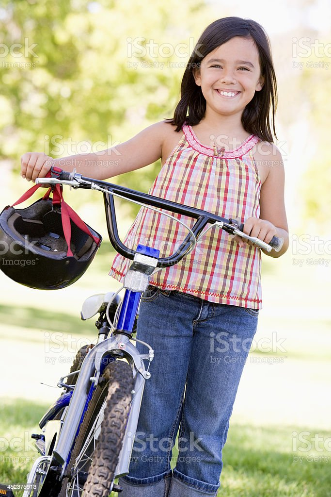 Young girl with bicycle outdoors smiling royalty-free stock photo