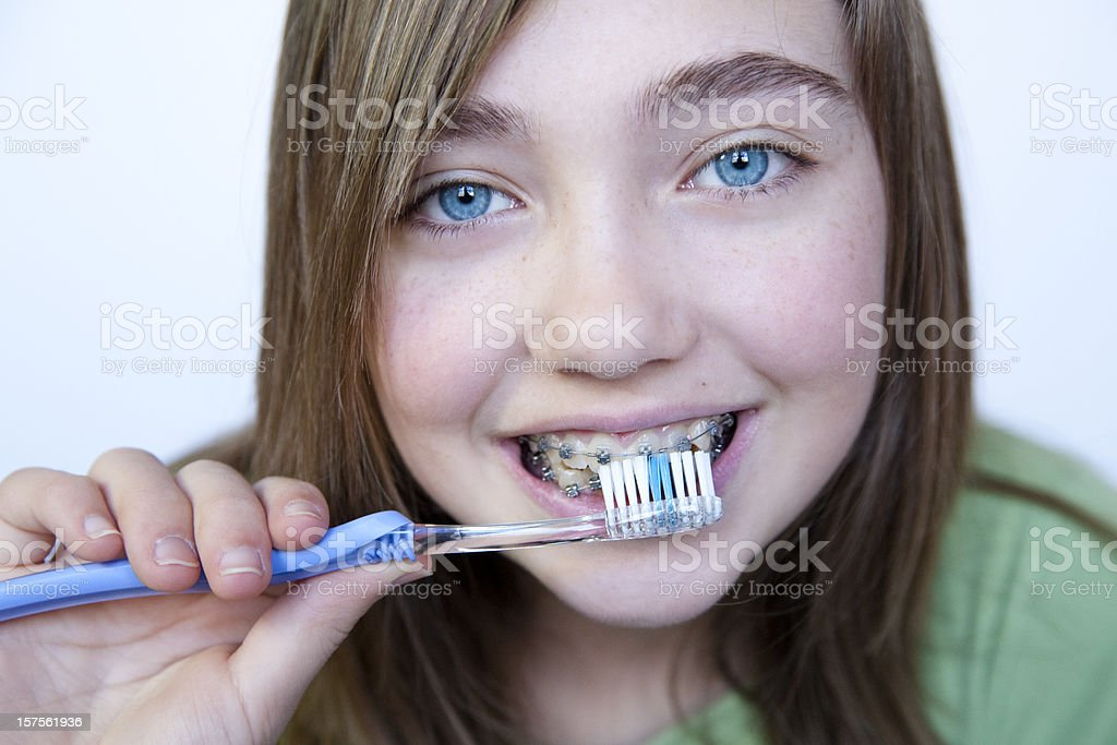 Young girl with blue eyes brushing teeth with braces. stock photo